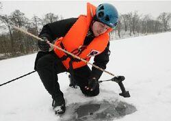 Policista z poříčního oddělení měří tloušťku ledu